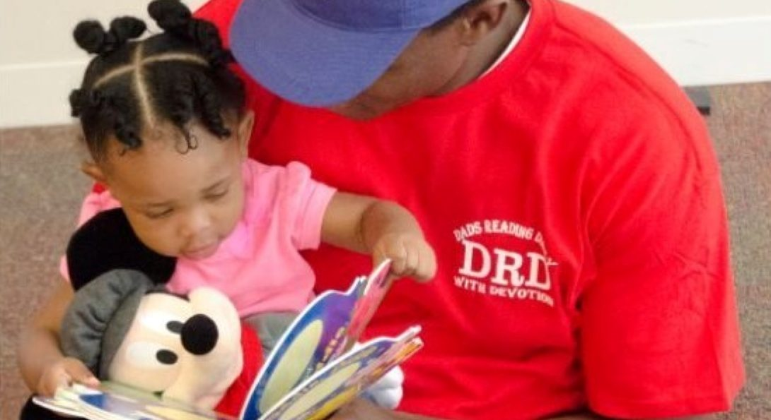 A dad reading a book for a little girl